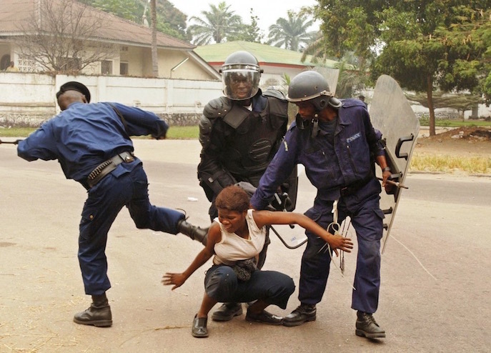 KINSHASA, -:  A policeman kicks a woman during a demonstration with a group of the main opposition Union for Democracy and Social Progress (UDPS) demonstrators, 30 June 2006, in Kinshasa. A major dialogue involving the political elite of the Democratic Republic of Congo (DRC) from the president down was set to open Friday to ensure a smooth run-up to the country's first democratic elections in 45 years. AFP PHOTO / LIONEL HEALING  (Photo credit should read LIONEL HEALING/AFP/Getty Images)